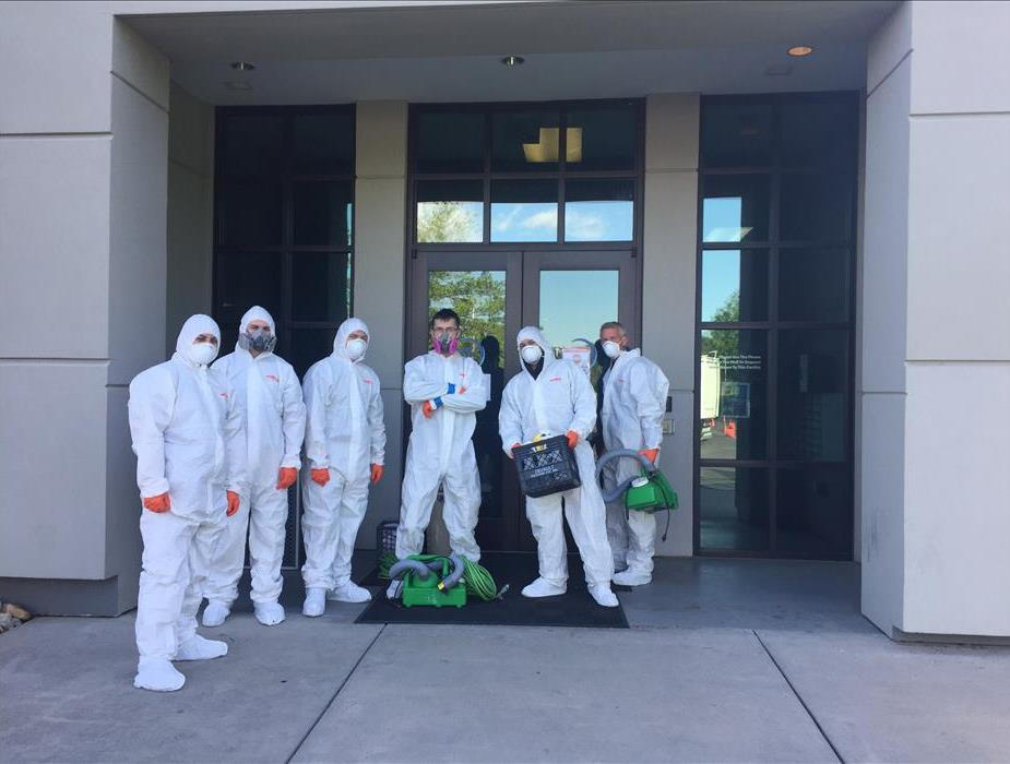 6 people stand in front of a building wearing personal protective equipment